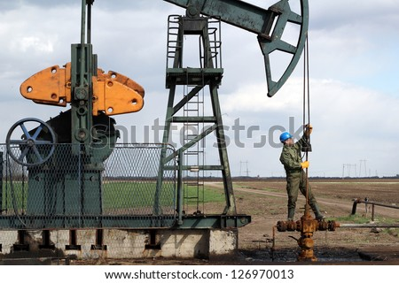 oil worker standing at pipeline and check pump jack - stock photo