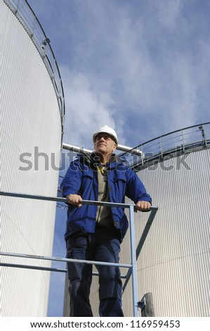 oil-worker standing on platform in fron of storage tanks, inside refinery - stock photo