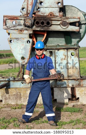 oil worker with pipe wrench posing - stock photo