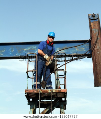 oil worker working on pump jack petroleum industry - stock photo