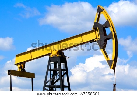Oilfield Pump Jack with a bright blue sky and clouds - stock photo