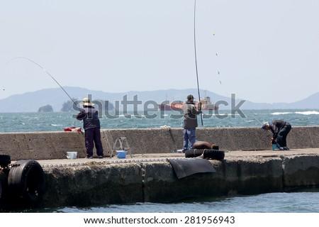 OKAYAMA, JAPAN - MAY 21: Men fishing off the pier on May 21, 2015 in Tamano, Okayam  - stock photo