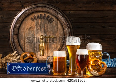 Oktoberfest beer barrel with beer mugs and pretzels on wooden background - stock photo