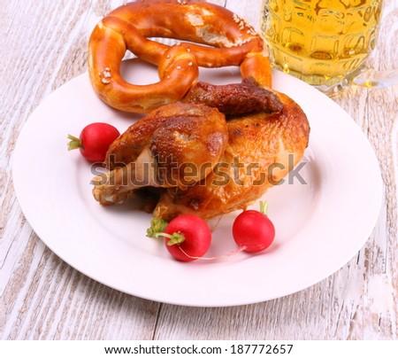 Oktoberfest chicken with pretzel, beer, radish, top view - stock photo