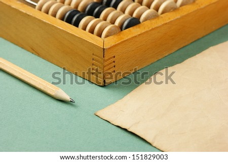 old abacus and notebook on the green background - stock photo