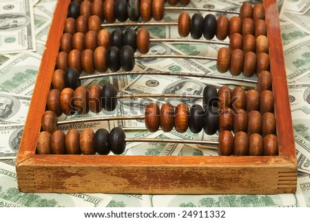 Old abacus on dollars, close-up, shallow depth of field. - stock photo