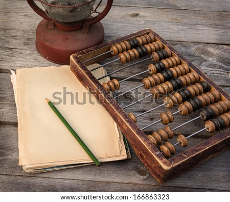 Old abacus, the paper with a pencil next to a kerosene lamp on a wooden table - stock photo