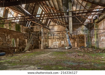 old abandoned and collapsed factory with rubble and debris - ruins of an ancient industrial building - stock photo