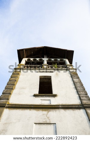 Old, abandoned building stone facade with tall windows and blue sky in the background - stock photo