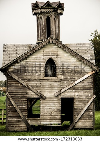 Old Abandoned Building 1. The facade of a small abandoned church or similar historic structure in a rural setting. - stock photo