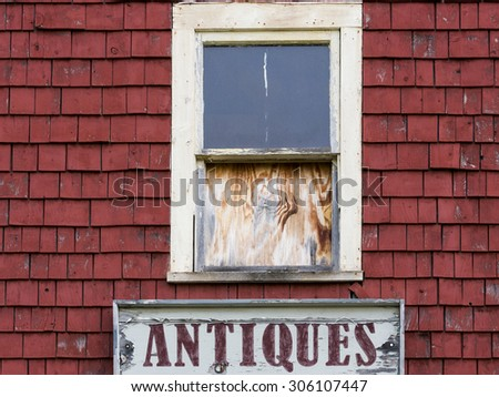 Old abandoned building with fading sign for antiques. - stock photo