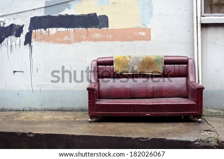 Old abandoned couch dumped on the street - stock photo