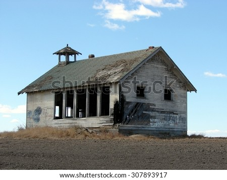 old abandoned country school house on the prairie - stock photo