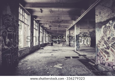 Old abandoned factory hall and graffiti - stock photo