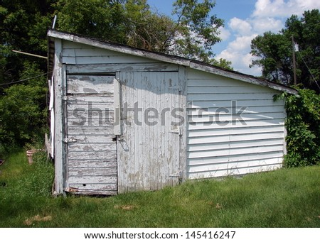 old abandoned farm buildings white storage shed - stock photo