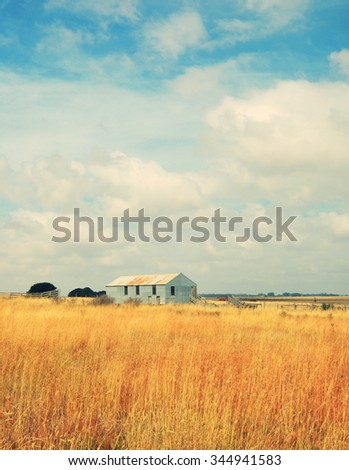 old abandoned farm in field - stock photo