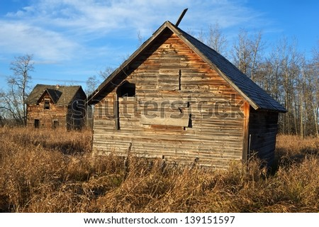 old abandoned farm with house and barn - stock photo