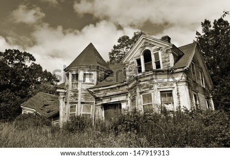 Old abandoned haunted house overgrown with weeds against a dark sepia sky - stock photo