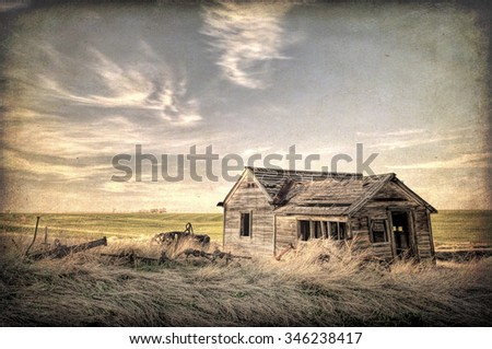 old abandoned house and farming machinery on Colorado prairie with texture effect finish - stock photo