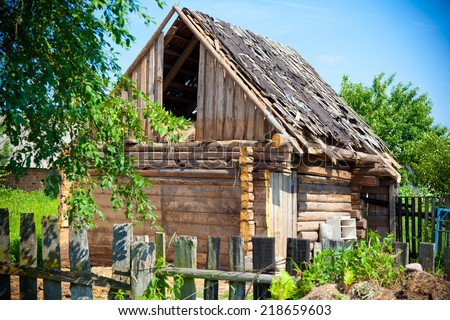 Old abandoned house from logs. Leaky, dilapidated roof - stock photo