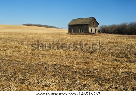 Old abandoned house in a harvested field in fall - stock photo