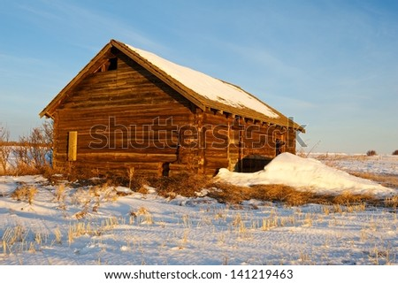 Old abandoned log cabin at sunrise in winter - stock photo