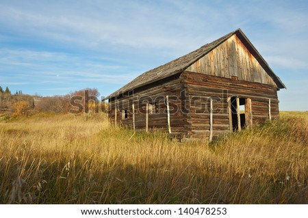 old abandoned log house in tall dry grass on a hillside - stock photo