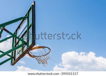 Old abandoned metal basketball playground stand on blue sky background - stock photo
