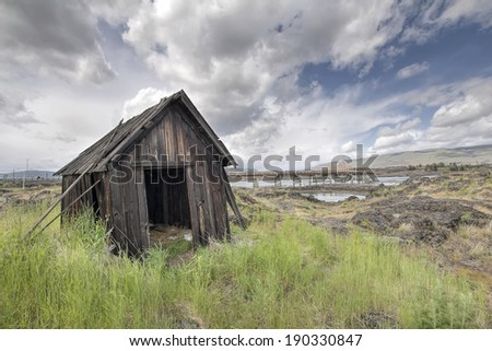 Old Abandoned Native American Fishing Shacks Along Columbia River by the Dalles Bridge in Oregon - stock photo