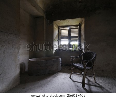 old abandoned room with chair and bathtub - stock photo