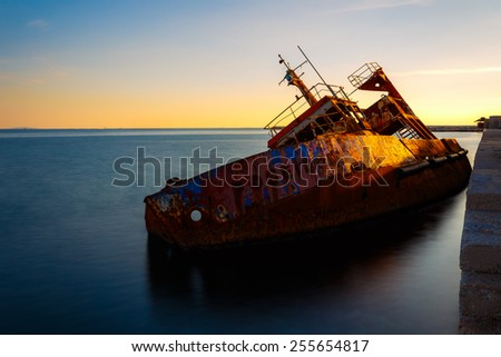 Old abandoned shipwreck near Kifisos river, Greece against a colorful sky, long exposure photograph - stock photo