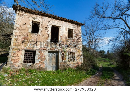 Old abandoned stone house ruins in countryside in Greece against a blue sky - stock photo