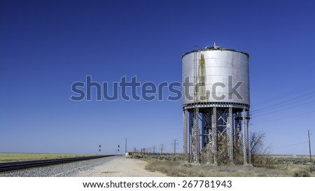 Old abandoned water tank and rail tracks - stock photo