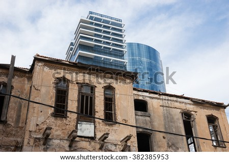 Old abandoned wrecked house and modern building at backgrounds. Tel Aviv (Israel). Time concept.  - stock photo