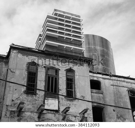 Old abandoned wrecked house and modern building at backgrounds. Tel Aviv (Israel). Time concept. Aged photo. Black and white. - stock photo
