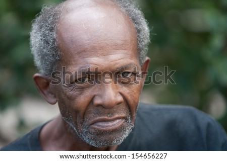 Old african american homeless man outdoors with sad eyes. - stock photo