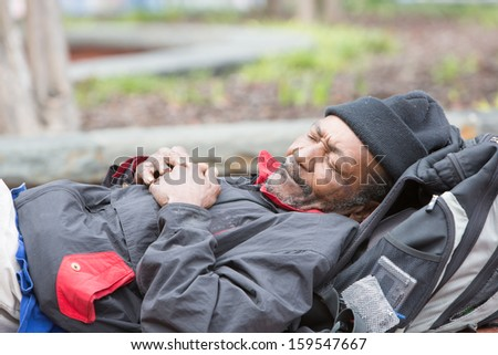 Old african american homeless man sleeping outside during the day. - stock photo
