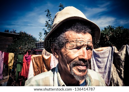 old african man wearing a khaki hat with washing on the line behind him - stock photo