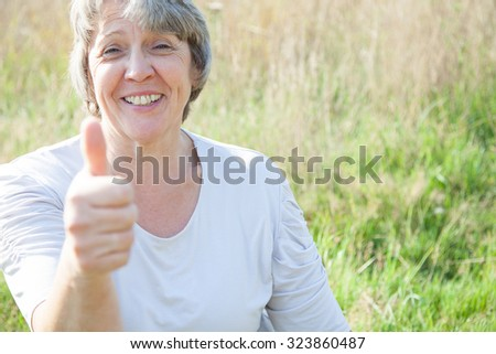 Old age woman showing thumbs up - stock photo