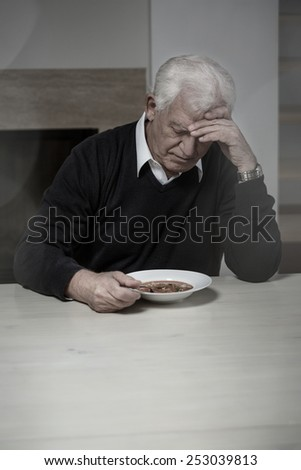 Old aged and lonely man eating soup - stock photo