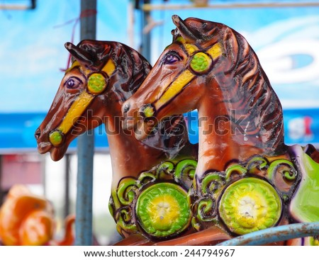old aged colorful riding animals horses rabbits ducks toys in a playground as circus carousel in a country fair in LOY KRATHONG Festival THAILAND.  - stock photo