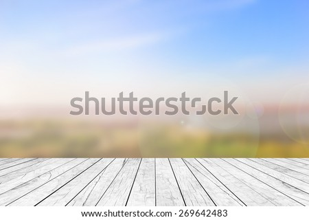 old aged surface of white vintage wooden perspective desk table top with blurred fine nature landscape background,promote,show advertise goods products item stuff banner template on display montage - stock photo