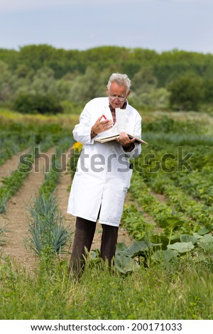 Old agronomist in white coat writing notes in book in field - stock photo