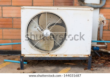 Old air compressors are located outside of building - stock photo