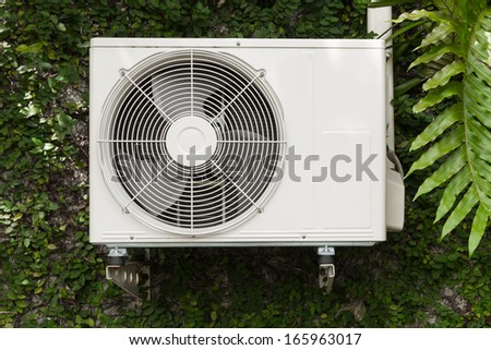Old air compressors are located outside of building and ivy - stock photo