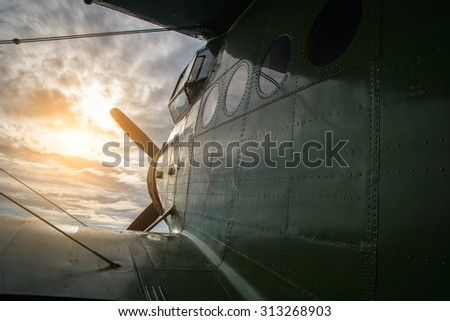 Old aircraft flying in a cloudy sky by sunset - stock photo
