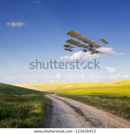 Old airplane flying above the beautiful green field - stock photo