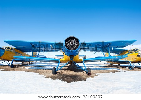 Old airplanes parked on a meadow with snow in a sunny day - stock photo