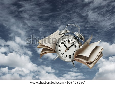 Old alarm clock flying with page wings, time flies concept - stock photo