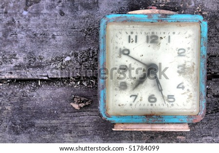 Old alarm on wooden board - stock photo